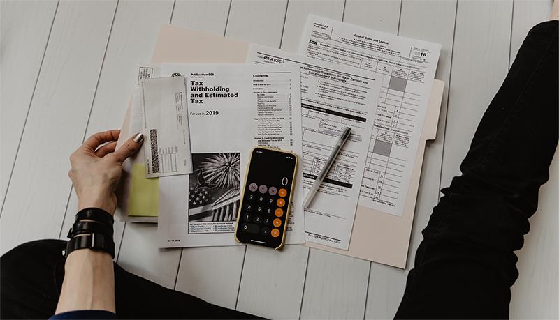 'n foto van 'n persoon wat met 'n belasting verklaring en sakrekenaar sit, gereed om belasting berekeninge te doen